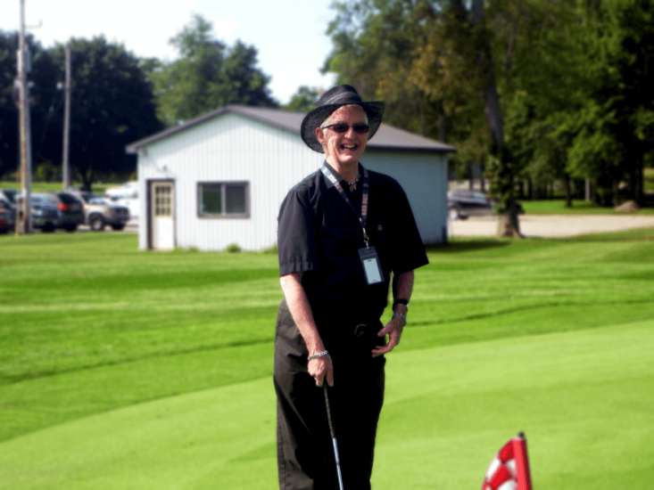 Photo of a man dressed in black holding a golf club. He is on a golf course and there is a white building behind him.